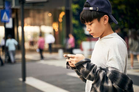 Photo for teenage asian child looking at cellphone while walking on street - Royalty Free Image