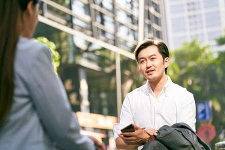 Photo pour asian businessman and businesswoman conversing outdoors - image libre de droit