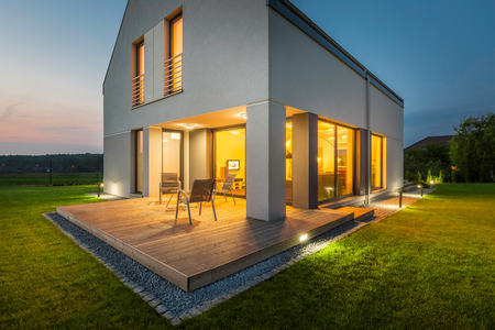 Foto de External view of a new house at night with patio and outdoor lighting - Imagen libre de derechos