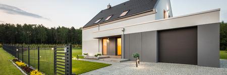 Foto de External view of stylish family house with fence, garage, stone driveway and garden, panorama - Imagen libre de derechos
