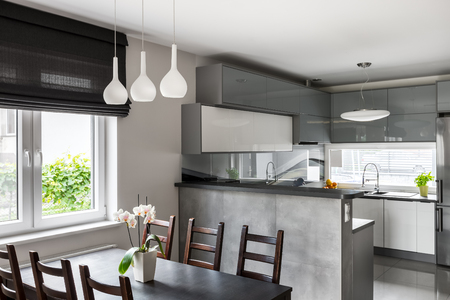 Photo pour Simple dining set, decorative pendant lamp and roller blinds, light open kitchen in the background - image libre de droit