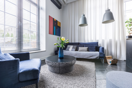 Photo pour Living room with blue upholstered furniture, window blinds and white net curtain - image libre de droit