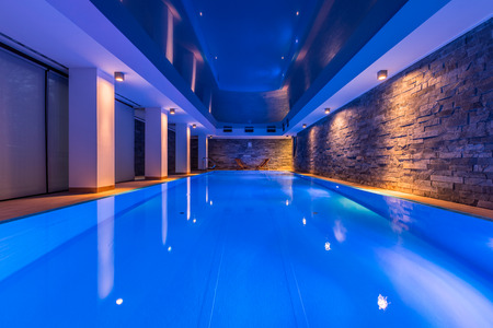 Photo pour Swimming pool with decorative led lights and brick wall - image libre de droit