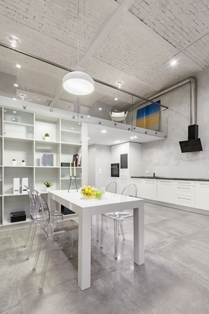 Loft interior with white table, transparent chairs and functional open kitchen