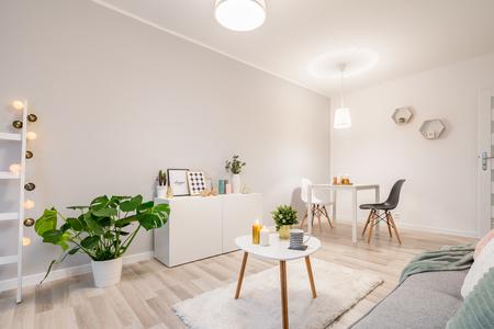 Foto de White living room in scandinavian style with couch, table and cabinet - Imagen libre de derechos