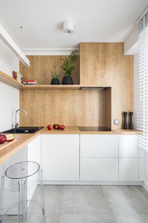 Foto de White, modern kitchen with wooden furniture and big window - Imagen libre de derechos