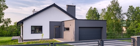 Foto de Panoramic view of stylish villa with fence, garage and lawn - Imagen libre de derechos
