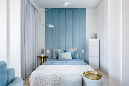 Photo for Narrow blue and gray bedroom with double bed and upholstered wall - Royalty Free Image
