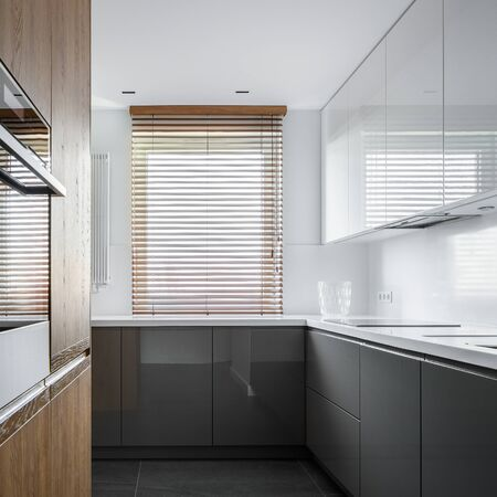 Photo pour Narrow kitchen with gray and white unit and wooden details - image libre de droit