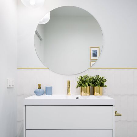 Photo pour Bright bathroom with round mirror, white cabinet with drawers and blue and golden decorations - image libre de droit