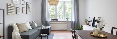 Foto de Stylish and small living room in gray and white with big window, panorama - Imagen libre de derechos