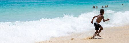Photo for Panorama of boy running away from big ocean wave at the beach - Royalty Free Image