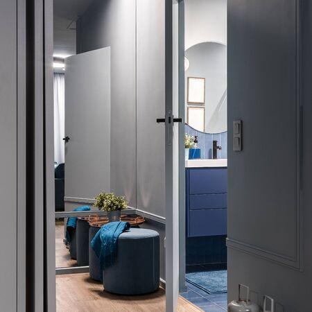 Photo for Corridor interior in gray with big mirror wall and open bathroom door - Royalty Free Image