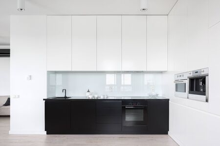 Photo for Elegant and simple kitchen with black and white cupboards - Royalty Free Image