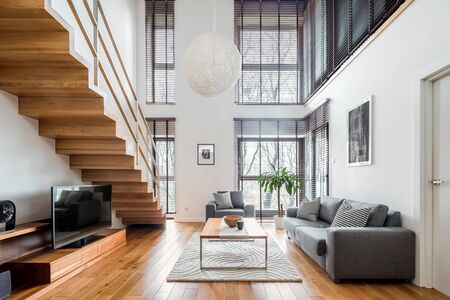 Photo pour Two-floor apartment with spacious living room with wooden stairs, hardwood floor and many, big windows - image libre de droit