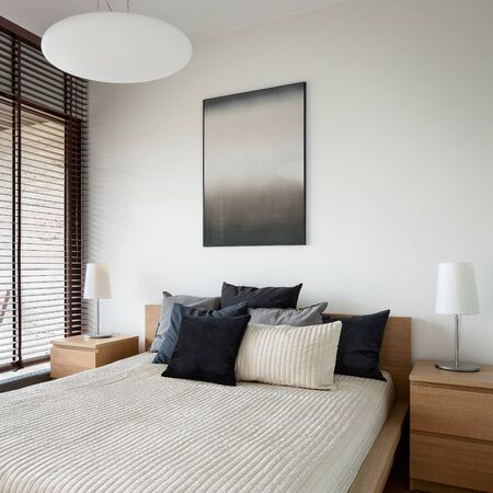 Photo pour Big and comfortable bed in bright bedroom and two wooden nightstands with lamps - image libre de droit