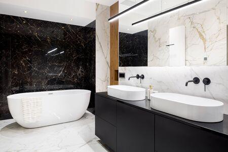 Photo pour Luxury bathroom with dark and bright marble tiles and big bathtub - image libre de droit