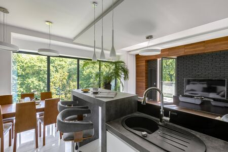 Photo pour Elegant kitchen with gray countertops and wooden dining table open to living room with big window wall and tv - image libre de droit