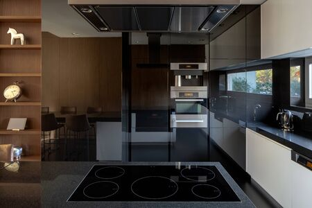 Photo pour Elegant kitchen with mirrored wall and induction hob with five burners - image libre de droit
