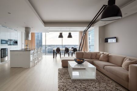 Photo pour Modern and elegant apartment with big corner sofa, stylish black lamp, luxury kitchen area and dining table in one spacious room with big window and amazing city view - image libre de droit