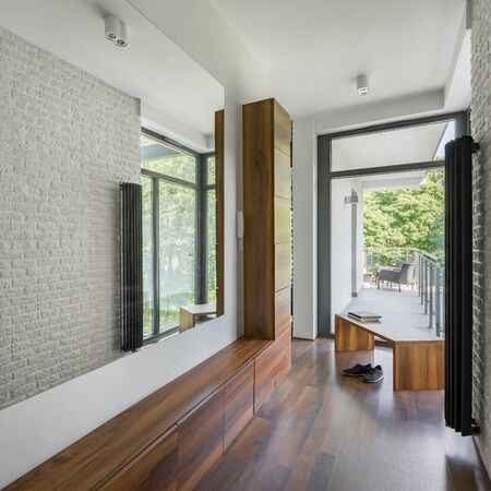 Photo pour Home corridor with long mirror, white brick wall, big window and wooden floor, cabinets and bench - image libre de droit