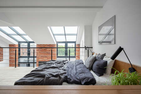 Photo pour Simple bedroom on mezzanine in loft style apartment with big windows and exposed red brick on the wall - image libre de droit
