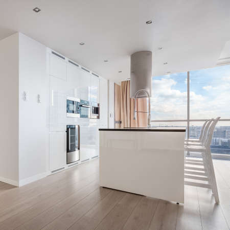 Photo for White shiny kitchen with big kitchen island and exhaust hood in apartment with amazing city view - Royalty Free Image