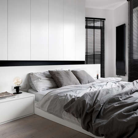 Photo pour Designed bedroom with white wardrobe, bedside table and big bed, gray bedclothes, wooden floor and black window blinds - image libre de droit