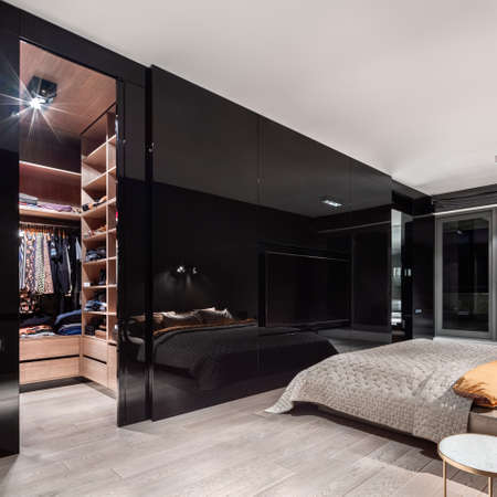 Photo pour Luxury bedroom with walk in closet with wooden shelves behind stylish, black and mirrored wall - image libre de droit