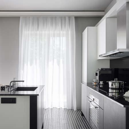Photo pour Modern black and white kitchen with big windows behind white curtains and with black and white kitchen island with sink and black and white furniture with black countertops - image libre de droit