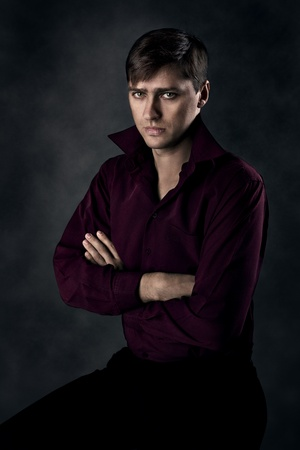 Handsome man sitting over grey background with crossed hands. Seriously looking at camera.
