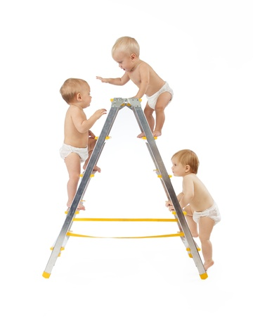 Photo for group of babies climbing on stepladder over white background - Royalty Free Image