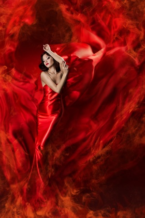 Beautiful woman in red waving silk dress as a fire flame. Looking down.