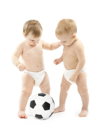Photo pour Two babies playing soccer ball over white background  Kids physical development - image libre de droit
