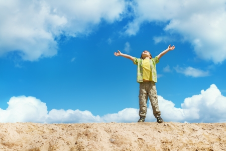 Foto de Happy child standing on the top with hands raised up  Happiness and freedom concept  - Imagen libre de derechos