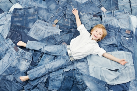 Happy child on jeans background. Denim fashion
