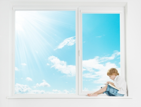 Foto de Window sunshine sky. Child on windowsill reading book.  - Imagen libre de derechos