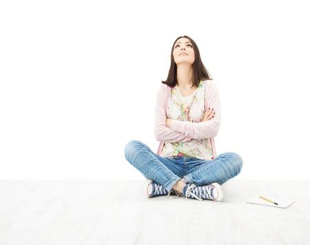 Beautiful girl teenager thinking sitting on floor. White background