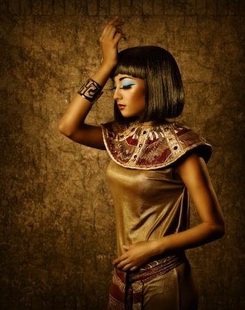 Beautiful egyptian woman bronze portrait over grunge dark gold background