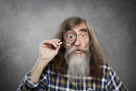 Senior old man looking through zoom magnifying glass  Funny elder amazement investigation or test vision loss