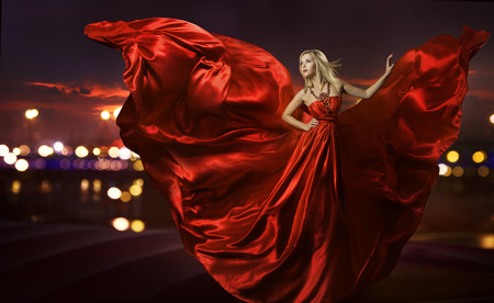 Photo pour woman dancing in silk dress, artistic red blowing gown waving and flittering fabric, night city street lights - image libre de droit