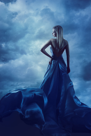 Photo pour Woman Back Portrait in Evening Dress, Lady in Silk Gown, Cloth Flying over Blue Sky, Night Clouds - image libre de droit