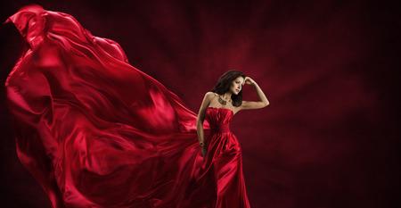 Foto de Red Dress, Woman in Flying Fashion Silk Fabric Clothes, Model Posing with Blowing Waving Cloth, Beauty Concept - Imagen libre de derechos