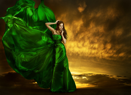 Woman Fashion Dress Fluttering On Wind, Elegant Girl Portrait, Model Posing In Green Silk Gown Fabric, Cloth Waving Over Night Sky