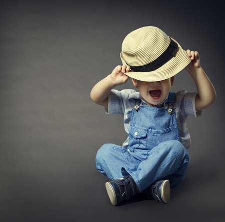 Baby Boy in Fashion Jeans, Hat Covered Eyes. Child Beauty Style, Well Dressed Boy Sitting over Gray Background