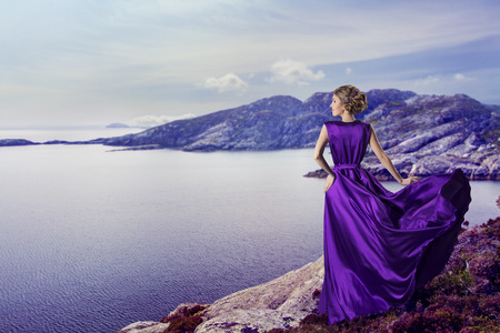 Woman in Purple Dress Looking to Mountains Sea, Waving Gown Flying on Wind, Elegant Girl Waiting on Coastの写真素材