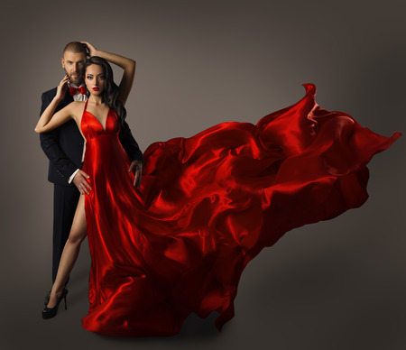 Fashion Couple Portrait, Woman Red Dress, Man in Suit, Long Waving Cloth Flying over Gray Background