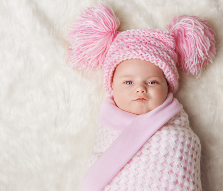 Photo pour Baby Girl Wrapped Up in Newborn Blanket, New Born Kid Bundled Hat, One Month on Carpet - image libre de droit