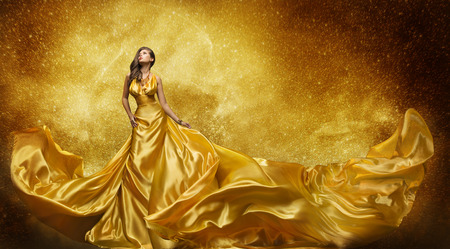 Photo pour Gold Fashion Model Dress, Woman In Golden Silk Gown Flowing Fabric, Beautiful Girl on Stars Sky looking up - image libre de droit