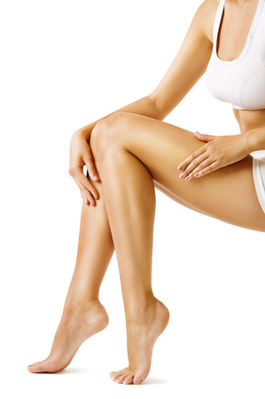 Foto de Woman Body Legs Beauty, Model Sitting on White, touch Leg Skin - Imagen libre de derechos